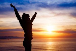 woman with outstretched arms at sunset on a beach - life after rehab - Valley Recovery Center of California - Sacramento Drug Rehab Center
