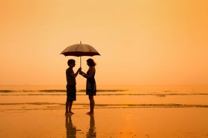 a couple on the beach at sunset under an umbrella - enabling behavior and codependency - valley recovery center of california - sacramento drug addiction treatment center