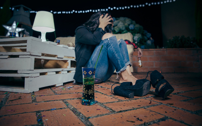 binge drinking and addiction - woman on floor after party - valley recovery center