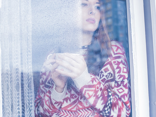 Natural Remedies for the Winter Blues - woman looking out at the snow