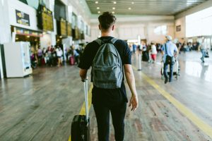 Going to Rehab Away from Home: What You Need to Know - young man with luggage at airport facing away