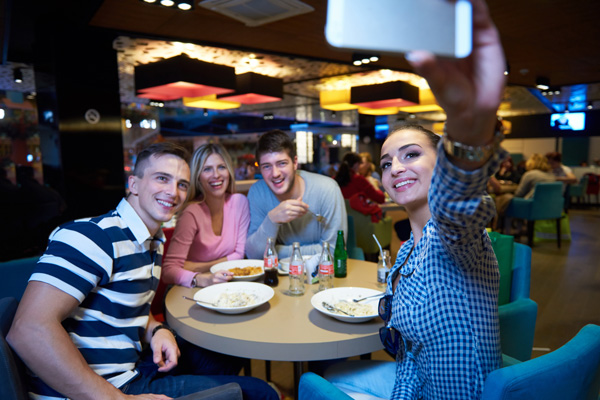 How to Socialize When Sober - friends eating while one takes selfie of the four of them