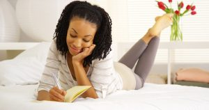Journaling for Emotional Awareness - woman laying on bed writing in journal
