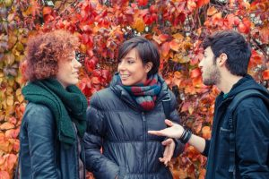 three people talking outdoors
