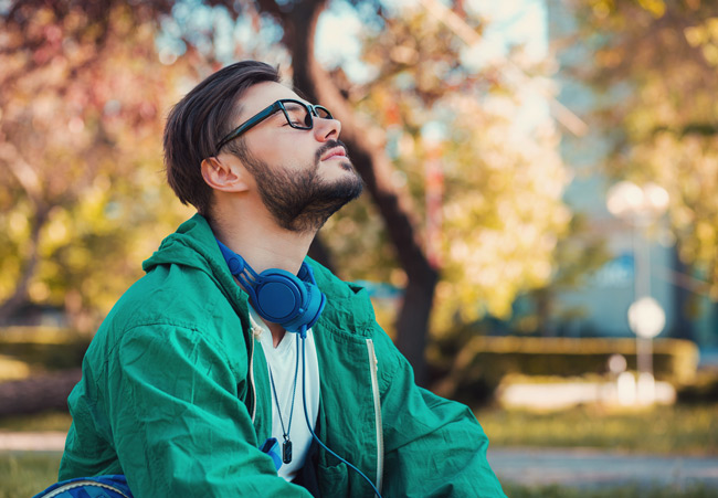 brunette bearded man with glasses in green coat taking deep breath outdoors - mental health