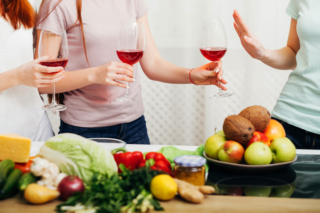 women drinking wine in kitchen - woman offers friend wine and she declines - social