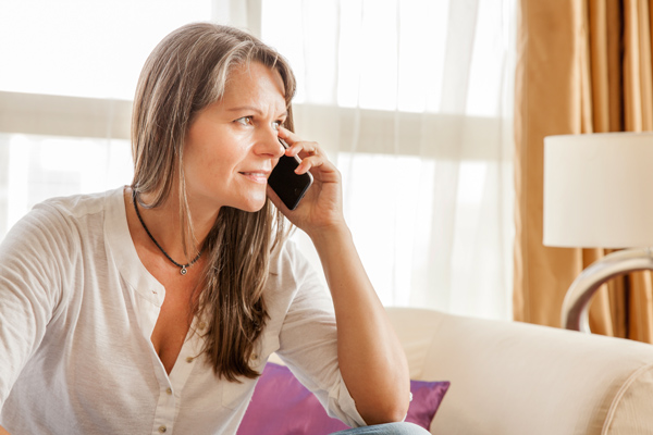 pretty middle-age woman sitting on couch talking on cell phone - cope with stress