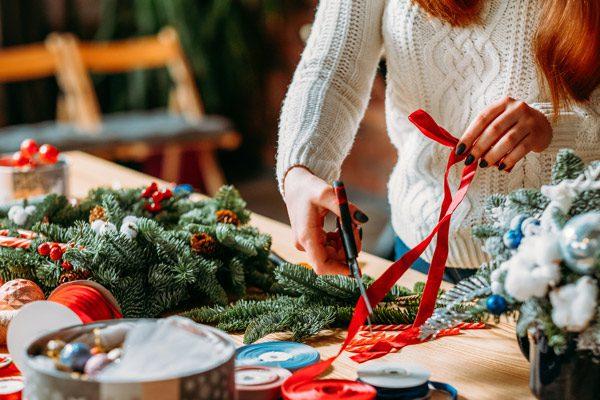 woman cutting ribbon for wreath - holiday season