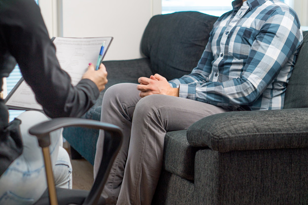 man sitting in therapy appointment with psychiatrist - evidence-based