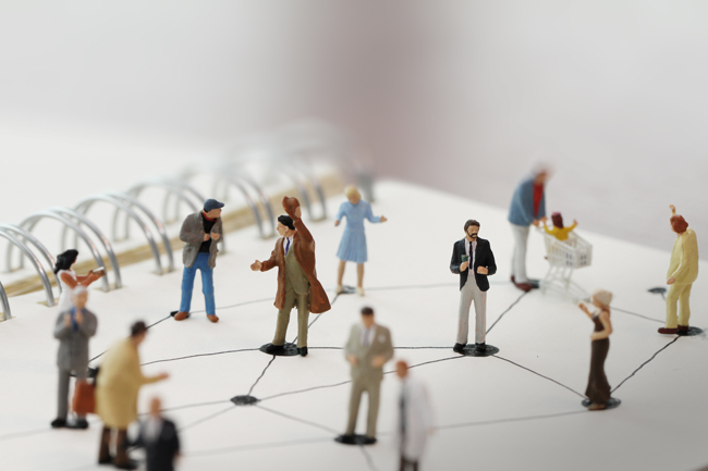 miniature figures set on paper representing social networking - social distancing