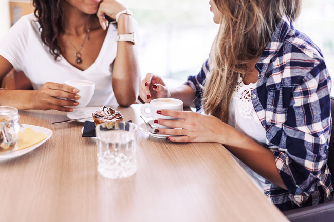 two woman talking over coffee - amends