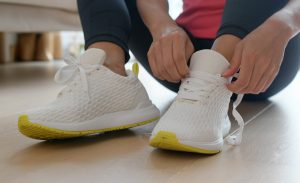 closeup of woman putting on running shoes - exercise