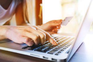 closeup of woman entering credit care info into laptop - cross addiction